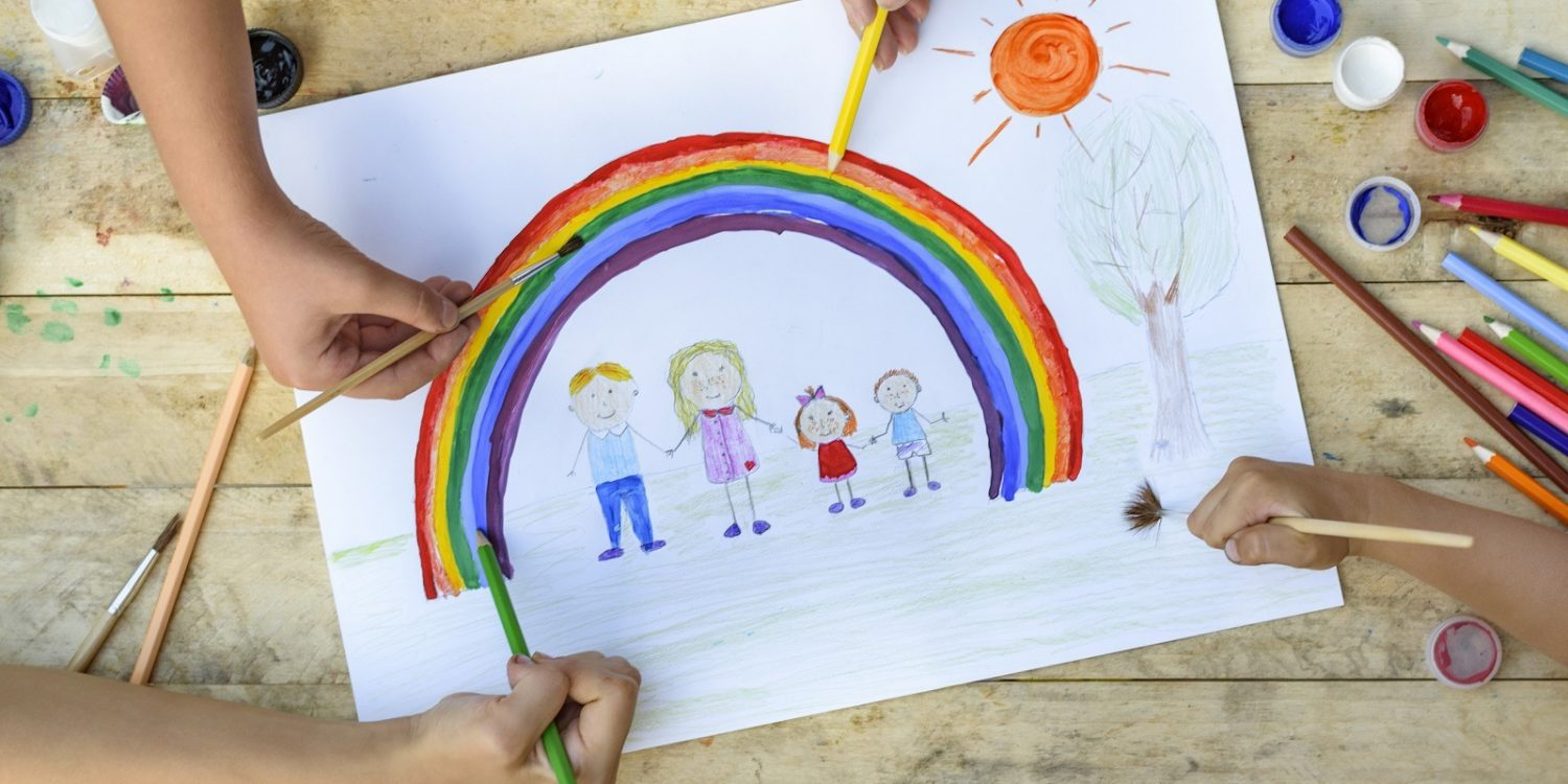 Happy family concept. Co-creation. Children hands draw on a sheet of paper: father, mother, boy and girl hold hands against background of rainbow and sunny sky. Close-up