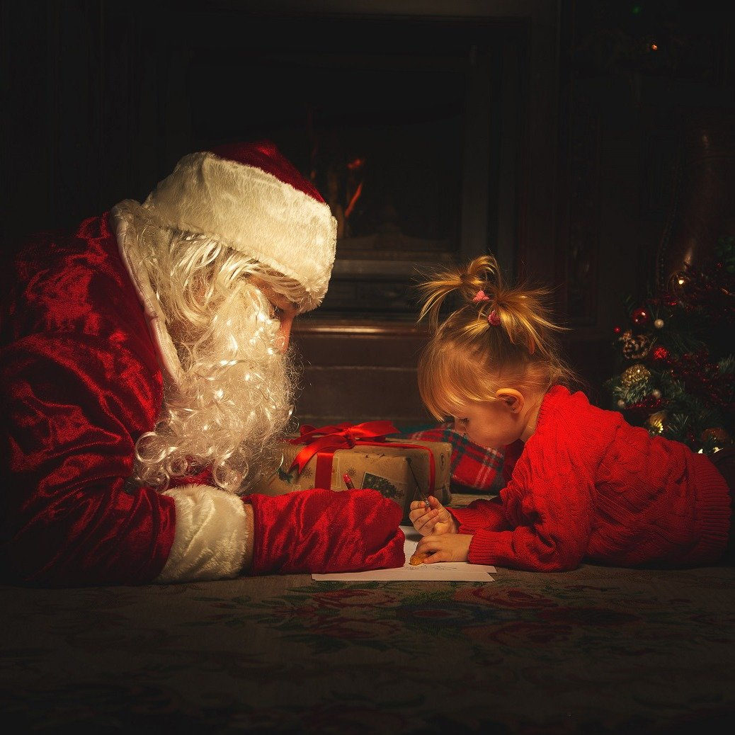 Real Santa Claus is playing with children near the Christmas tre