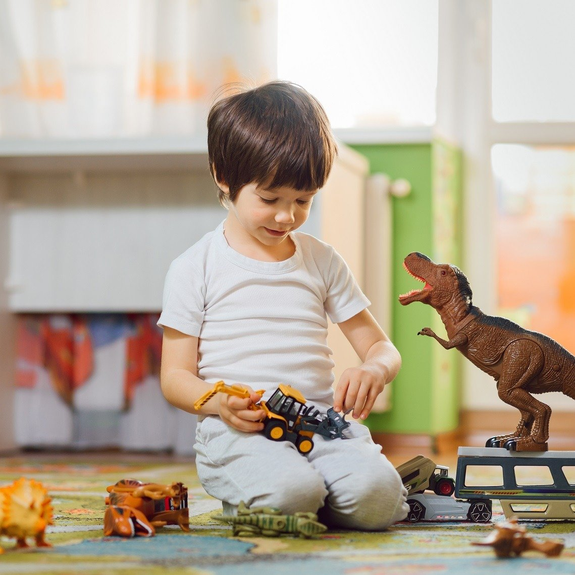 Adorable toddler playing with dinosaurs around lots of toys at home. Stay home.